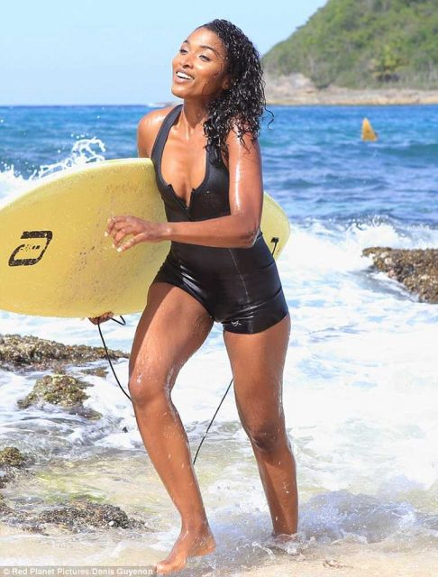Death in Paradise: Sara Martins as DS Camille Borday in swinsuit with surfboard